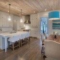 white-cabinet-kitchn-with-wood-ceiling-and-flooring-and-dining-island